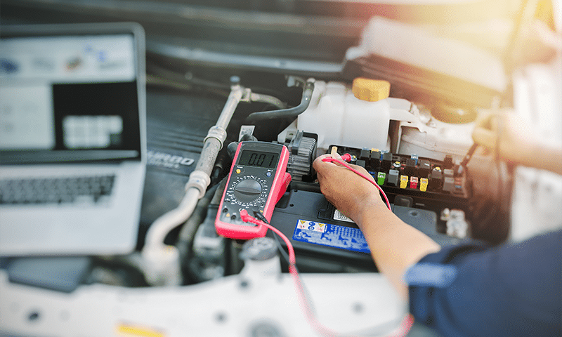 mercedes electrical repair technician with meter connected to fusebox troubleshooting electrical problem