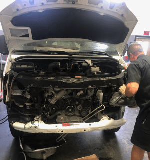 white sprinter van in shop with hood lifted and mechanic repairing engine compartment parts