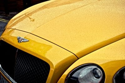 yellow bentley exotic car hood with bentley hood ornament and driver headlight and rain drops