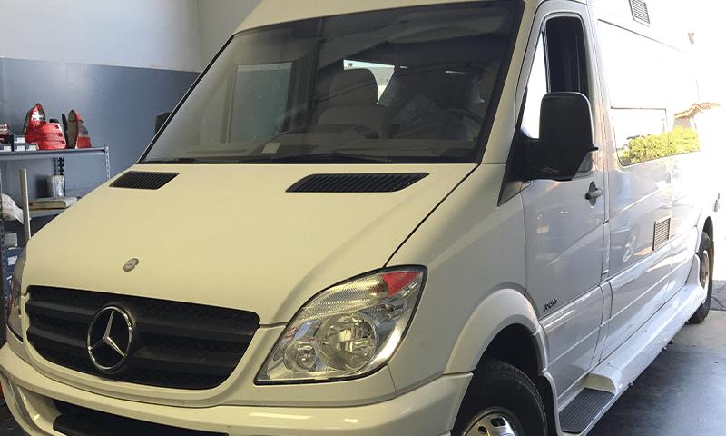 white mercedes-benz sprinter van in shop for repair